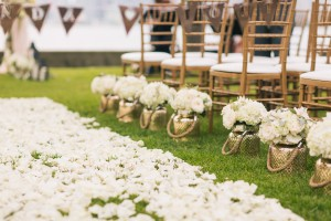 Gold plant pots with clusters of white flowers to decorate the aisle