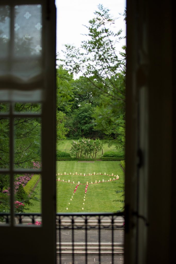 Looking out from a window into a garden, decorated with flowers and rose pedals in the shape of a heart