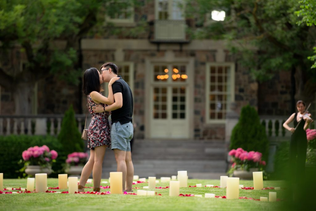 A man and a woman kissing in a garden surrounded my flower pedals and candles