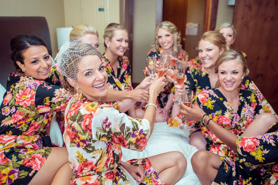bridesmaids and the bride all in robes doing a cheers