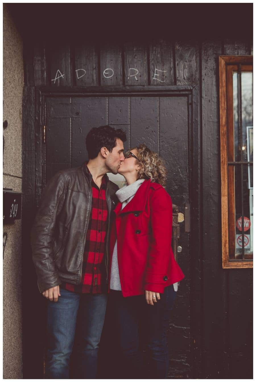 Couple in red kissing in front of old wooden door with adore written in chalk above their heads