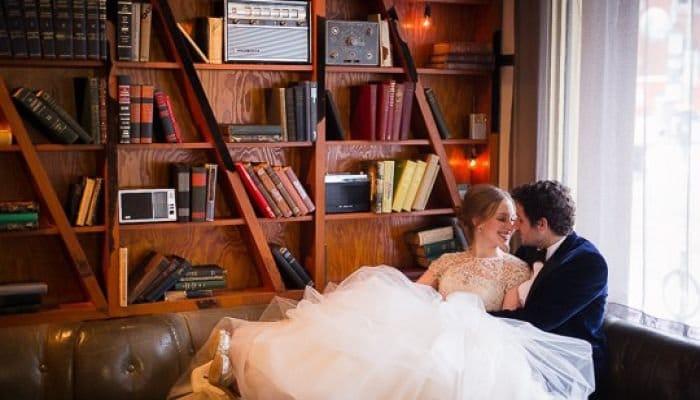 Bride & Groom next to a book shelf